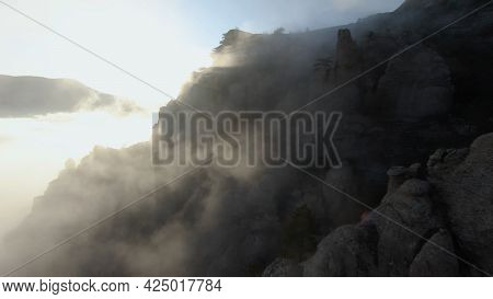Flying By Rocky Mountains With Low Clouds. Shot. Extreme Flight On Drone Near Rocky Slopes Of Mounta