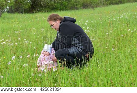 The Little Infant Girl In A White Cap And Pink Clothes Is Smiling  On Green Meadow