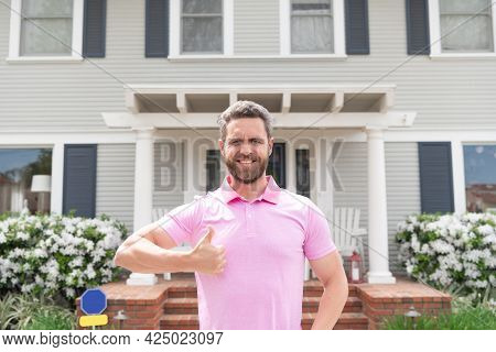 Happy Owner Show Thumb Up. Ownership. Confident Man Outside New American Home.