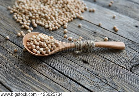 Uncooked Dried Legume Chickpeas In Spoon With Heap Of Garbanzo Bean On Wooden Table. Vegetarian Supe
