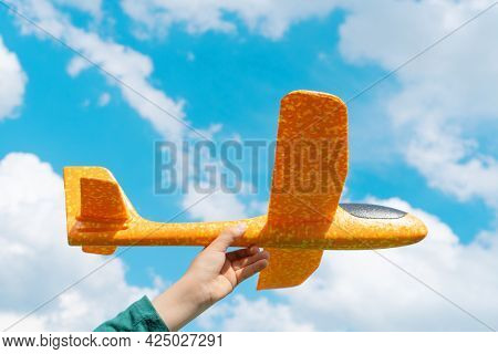Child Hand Holding Cheerful Orange Toy Plane On Blue Sky Background. Happy Childhood, Freedom And As