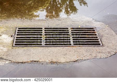 Faulty Drainage System With A Hatch Grate For Drainage Of Rainwater On The Road With Puddles After R