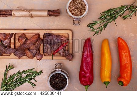Jerky Snacks On Wooden Board, Red, Orange And Yellow Papper, Meat Sticks, Peppercorns In Glass Jars