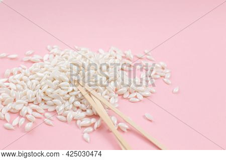 Hair Removal Wax Beads And Wooden Stripes On Pink Background. Film Wax Granules And Wooden Spatula.