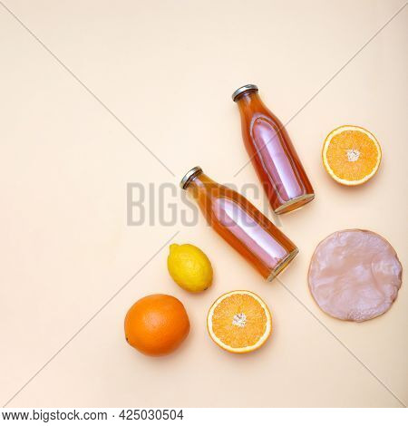 Two Bottles Of Kombucha Tea, Scoby And Citrus Fruits For Additional Flavors On Yellow Pastel Backgro