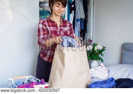 A Woman Selecting Clothes From Her Wardrobe For Recycle Or Donating To A Charity Shop. Woman Declutt