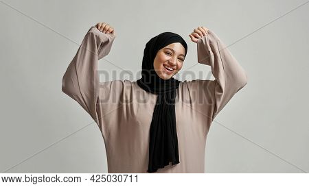 Happy Young Arabian Woman In Hijab Smiling Wide And Raising Hands While Looking At Camera On Light B