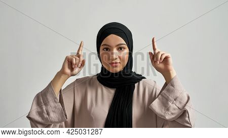 Happy Young Arabian Woman In Hijab Pointing Fingers Up While Looking At Camera On Light Background,