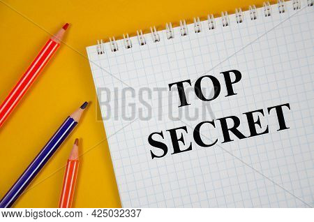 Top Secret Word Written On White Notepad And Yellow Background.text