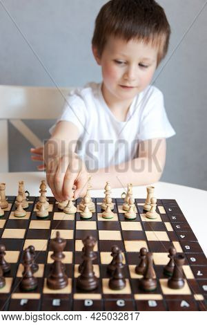 A Cute Caucasian Boy Of 6 Years Old Makes A Chess Piece Move. A Game Of Chess For The Development Of