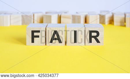 Fair Word On Wooden Building Blocks Lying On The Yellow Table, Concept
