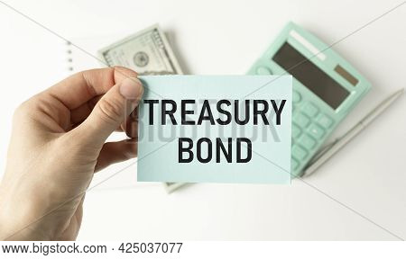 Treasury Bonds Word Written On A Piece Of Paper. A Woman Holds It And Points To The Word