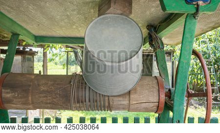 An Old Water Well With A Bucket In The Garden, A Metal Handle For Lifting Water From The Ground. Vil