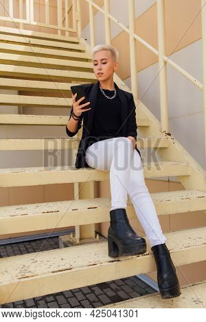 Young Stylish Business Woman With Short Hair And Nose Piercing Sitting On The Stairs