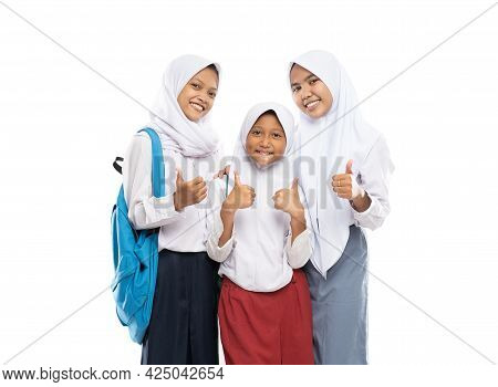 Three Girls In Veils Wearing School Uniforms Stand With Thumbs Up While Carrying Backpacks