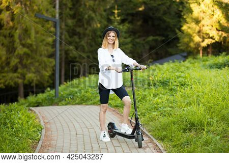 Side View Of Beautiful Young Blonde Woman In White Go To Work On Electric Scooter In City Summer.