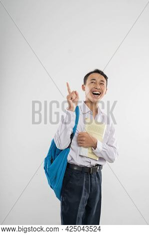 A Boy In Junior High School Uniform Looking Up With Finger Pointing When Carrying A Book And A Backp