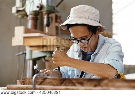 Concentrated Creative Young Man In Glasses Carving Wood With Chisel And Hammer In Workshop