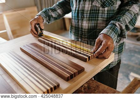 Hands Of Elderly Carpenter Measuring Walnut And Maple Wooden Pieces Fused Together For Making Edge G