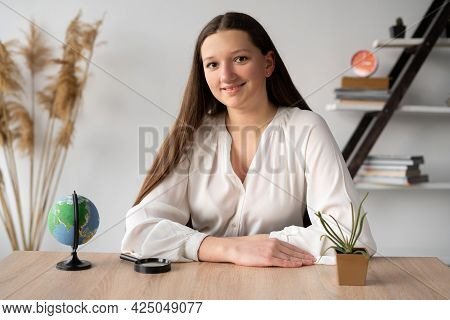 A Long-haired Girl Student Sitting At A Desk In The Office Listens To Or Watches An Online Lesson Wh