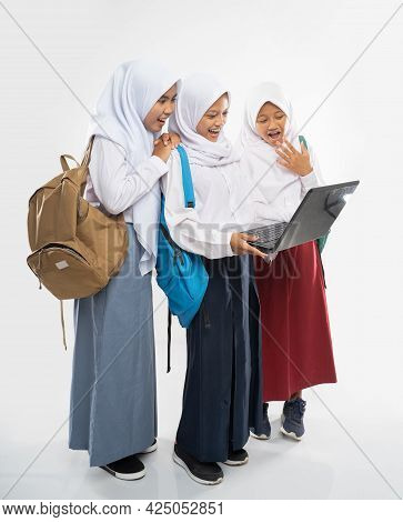 Three Veiled Girls Wearing School Uniforms Using A Laptop Computer Together While Carrying A Backpac