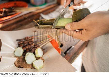 Sate Ayam Preparation Served With Rice Cake Or Lontong With Peanut Sauce On Food Paper