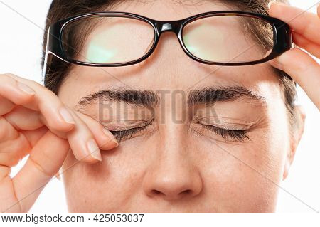 Ophthalmology. Close-up Of Woman's Face Scratches Her Painful Eyes, Taking Off Her Glasses. The Conc