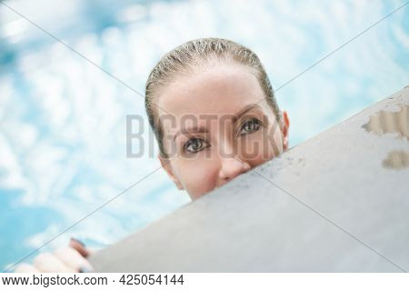 Wellness - happy white woman in her 30s relaxing swimming in wellness resort pool, smiling.