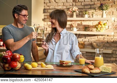 Couple at home in kitchen at morning preparing breakfast and clinking with champagne.