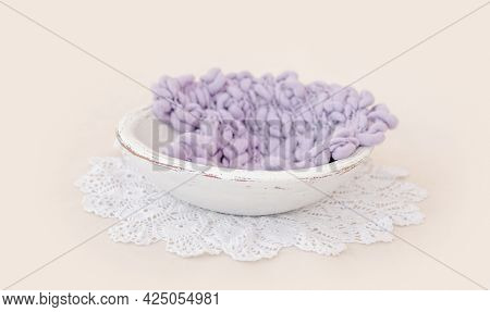 Beautiful backdrop for newborn photosession with flowers hydrangea. Digital composite with basin filled with knitted blanket isolated on light pink background