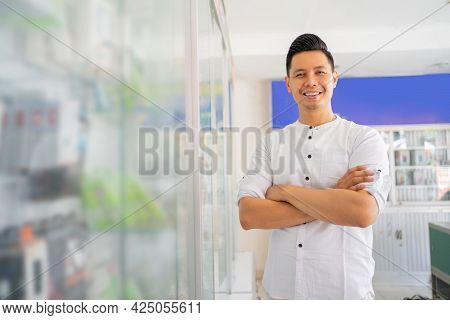 Handsome Asian Man Smiling With Crossed Hands Near Cell Phone Accessories Display Case