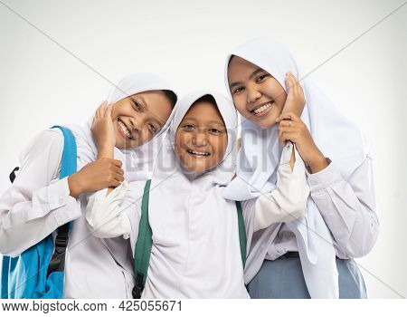 Three Girls In Headscarves Wearing School Uniforms Stand Smiling With Affectionate Gestures Of Each