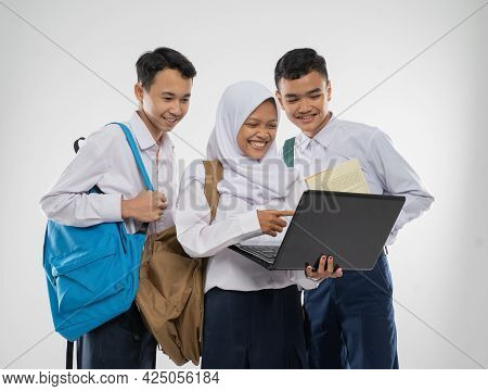 Three Teenagers In Junior High School Uniforms Smiling Using A Laptop Computer Together While Carryi