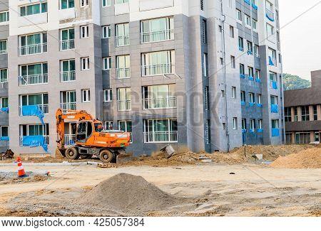Daejeon; South Korea; June 20, 2021: Doosan Backhoe Sits Idle Beside High Rise Building At Construct