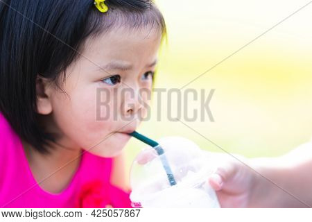 Head Shot Of Asian Kid Girl Sucking Sweet Coconut Smoothie. Mom Holding Glass To Feeding Daughter. B
