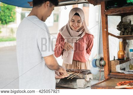 Woman Ordering Chicken Satay On The Street Food Seller
