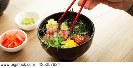 A Man Eats A Poke Salad With Tuna In A Bowl With Chopsticks. Place The Tuna Salad In A Bowl. Young M