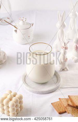 A Glass Of Milk On A Marble Plate On A White Table Cloth, Freshly Baked Cookies, Creamy Bubble Candl