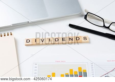 Dividends Payment Concept With Letters On Wooden Cubes. Still Life Of Office Workplace With Supplies