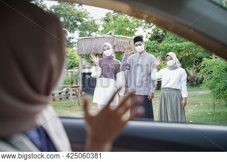 A Muslim Family Stands Waving To A Woman In A Headscarf In A Car
