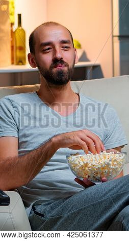 Man Late At Night In His Apartment Looking At Tv Entertainment, Laughing And Having Fun While Eating