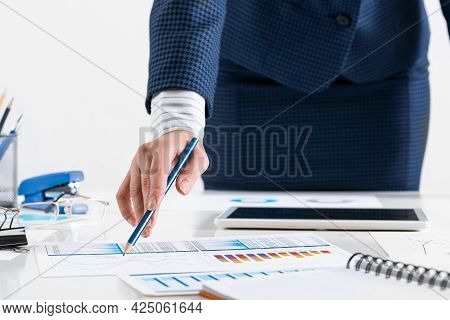 Businesswoman Standing Near Office Desk And Analyzing Financial Charts. Successful Corporate Manager