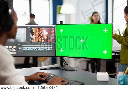 African Video Editor With Headset Editing Footage Using Pc With Greenscreen, Chroma Key Isolated Dis