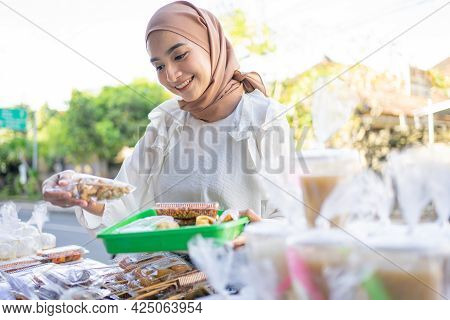 A Beautiful Girl In A Headscarf Holding A Snack Wrapped In Plastic Will Be Bought