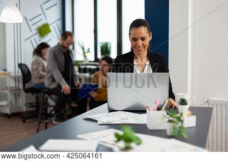 Happy Hispanic Lady Typing On Laptop Sitting At Desk In Start Up Business Office Drinking Coffee Whi