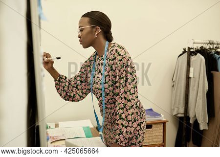 Young African Female Clothing Designer Writing Notes On A Whiteboard