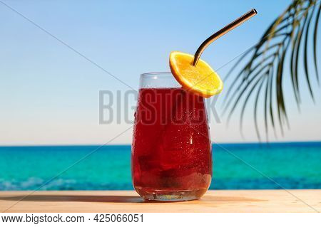 Rum Cocktail With Cranberry Juice On The Tropical Beach. Glass Of Alcoholic Refreshing Drink Decorat