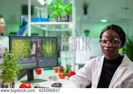 Portrait Of Biologist Researcher Woman In White Coat Looking Into Camera While Standing In Microbiol