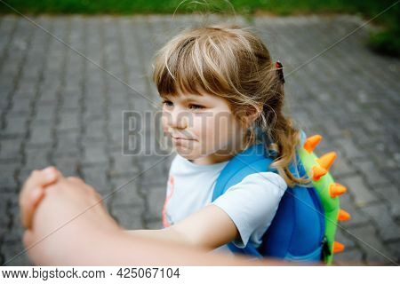 Mother Accompanies Toddler To Kindergarten Or Daycare. Caring Mother Holds Daughter Hand As She Goes