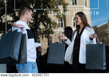 Portrait Of Young Woman And Man With Shopping Bags. Successful Shopping Concept. Young Couple After